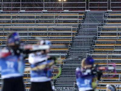 Biatlonistky strieľajú na strelnici pred prázdnou tribúnou počas šprintu žien