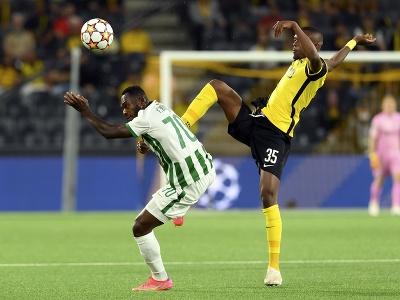 Hráč Young Boys Christopher Martins (vpravo) bojuje o loptu s Franckom Bolim z  Ferencvárosu v zápase play off Ligy majstrov