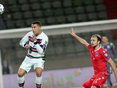 Cristiano Ronaldo hlavičkuje loptu pred hráčom Luxemburska