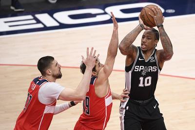 Na snímke vpravo hráč Spurs DeMar DeRozan pri streľbe, vľavo hráči Wizards, zľava Alex Len a  Raul Neto