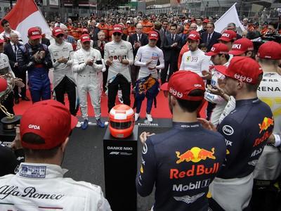 Na snímke piloti formuly 1 s červenými čiapkami s nápisom Niki tlieskajú pred podstavcom s helmou a nápisom Ďakujeme Niki po minúte ticha na počesť zosnulého kolegu Nikiho Laudu pred štartom Veľkej ceny Monaka F1 v Monte Carle