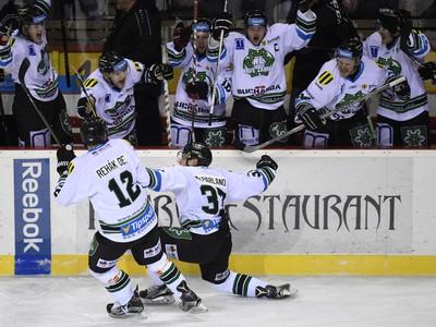 Hráč Nových Zámkov Nick McParland (druhý zľava na ľade) sa teší po góle spolu s hráčmi na striedačke