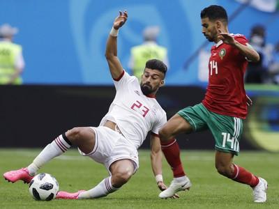 Ramin Rezaeian a Mbark Boussoufa v súboji o loptu