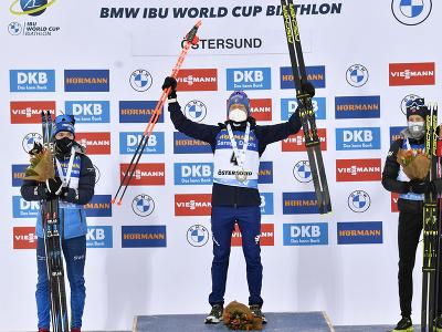 Taliansky biatlonista Lukas Hofer (uprostred) sa teší na pódiu po triumfe v piatkovom šprinte