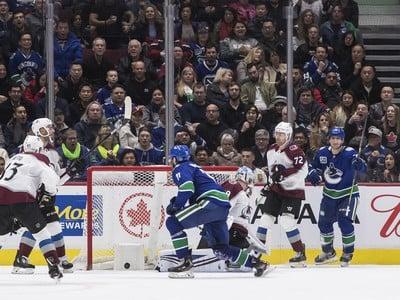 Zack MacEwan strieľa gól do bránky Colorada Avalanche brankárovi Pavlovi Francouzovi