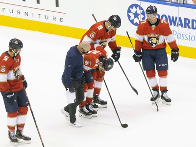 Zranený obranca Floridy MacKenzie Weegar odchádza za pomoci tímového lekára z ľadu