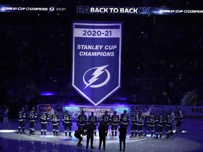 Hráči Lightning sledujú, ako sa na štadióne dvíha vlajka pre víťaza minulého ročníka NHL
