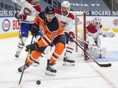 Joakim Nygard z Edmontonu vedie puk pred Tomášom Tatarom