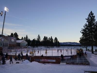 Svetlá začínajú svietiť na hraciu plochu po západe slnka počas zápasu pod holým nebom pri Lake Tahoe