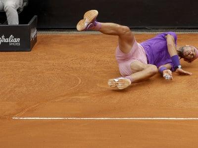 Španielsky tenista Rafael Nadal padá na zem po zakopnutí o čiaru v zápase proti Srbovi Novakovi Djokovičovi