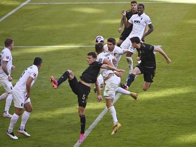 Robert Lewandowski v hlavičkovom súboji s hráčmi Augsburgu