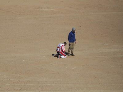 Portugalský motocyklista Joaquim Rodrigues kľačí na piesku po úmrtí svojho krajana Paula Goncalvesa