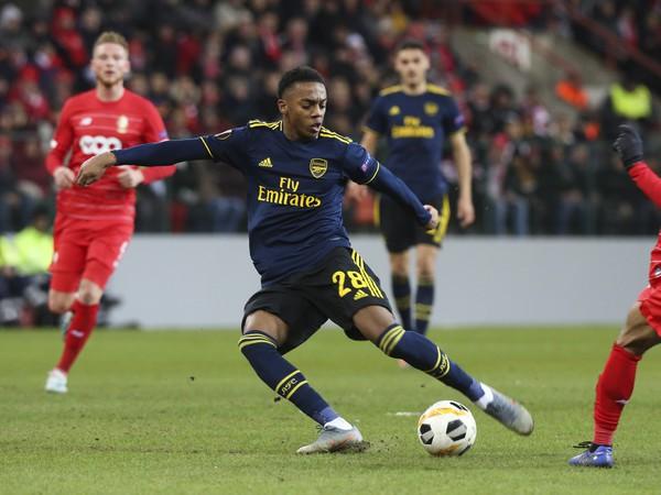 Hráč Arsenalu Joe Willock (uprostred) kope do lopty vedľa Mehdiho Carcelu z Liege