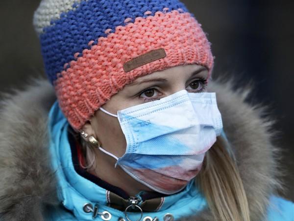Diváčka s ochranným rúškom na tvári pred šprintom žien
