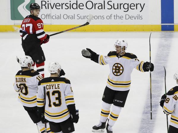 Nikita Gusev sleduje radujúcich sa hráčov Bostonu po tom, čo Connor Clifton (v strede) strelil gól