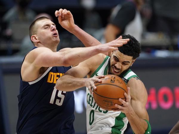 Útočník Bostonu Celtics Jayson Tatum (vpravo) a Nikola Jokič z Denveru Nuggets bojujú o loptu