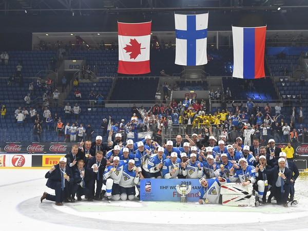 Fínski hokejisti pózujú s trofejou a zlatými medailami po víťazstve nad Kanadou