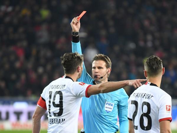 Hlavný rozhodca Felix Brych ukazuje červenú kartu kapitánovi Eintrachtu Frankfurt Davidovi Abrahamovi za vrazenie do trénera Freiburgu Christiana Streicha