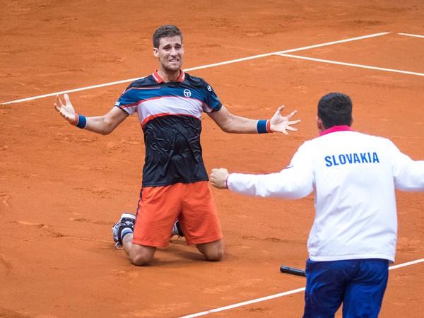 Slovenský tenista Martin Kližan a nehrajúci kapitán Dominik Hrbatý sa radujú z výhry