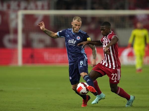 Hráč Slovana Joeri de Kamps (vľavo) bojuje o loptu s Aguibouom Camarom z Olympiacosu