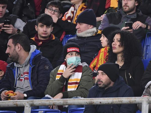 Futbalový fanúšik s ochranným rúškom na tvári