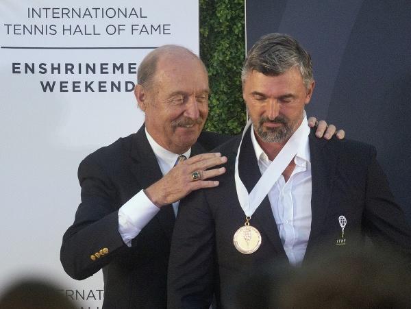 Goran Ivaniševič si preberá ocenenie od Stana Smitha