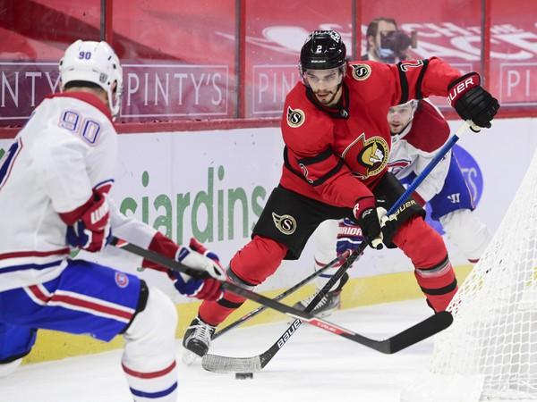 Tomáš Tatar v súboji o puk s hráčom Ottawy