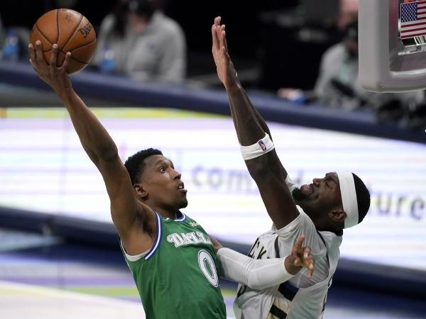 Hráč Dallasu Mavericks Josh Richardson (vľavo) strieľa na kôš cez Bobbyho Portisa z Milwaukee Bucks