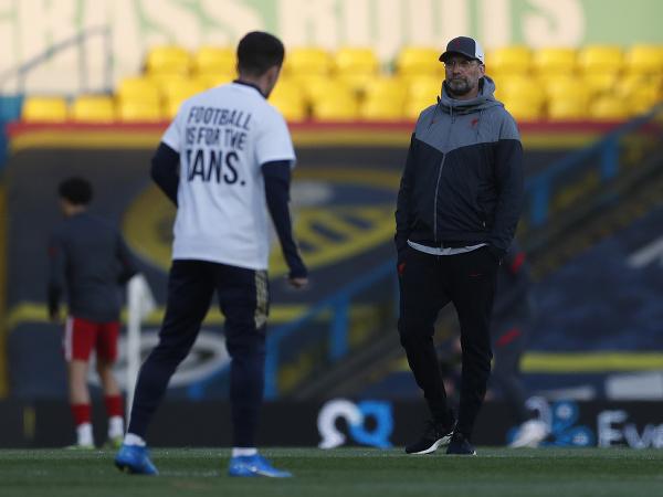 Jurgen Klopp a rozcvičujúci sa hráč Leedsu v špeciálnom tričku s protestnými nápismi