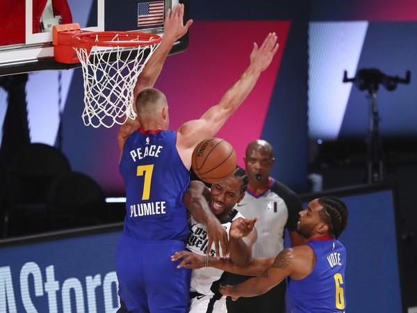 Hráč Los Angeles Clippers Kawhi Leonard (uprostred) sa pokúša strieľať cez Masona Plumleeho