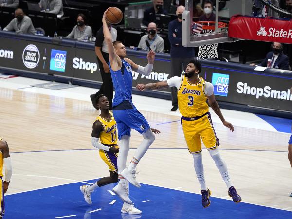 Hráč Dallasu Mavericks Kristaps Porzingis (uprostred) strieľa na kôš cez Dennisa Schroedera (17)