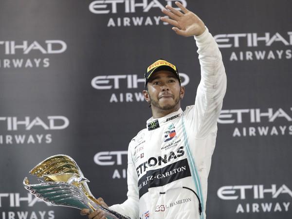 Lewis Hamilton oslavujúci s víťaznou trofejou