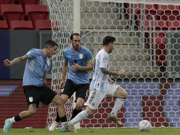 Lionel Messi uniká Diegovi Godínovi a Josému Gimenézovi