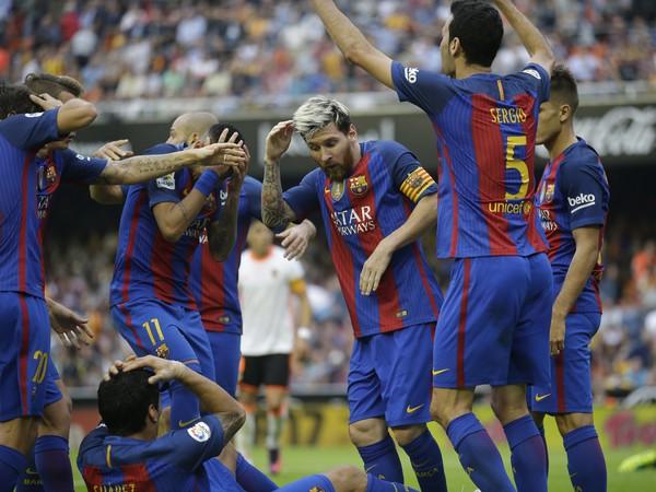 Futbalisti FC Barcelona sa chránia pred padajúcimi predmetmi, ktoré na nich hádžu diváci po tom, čo Lionel Messi (uprostred) premenil penaltu