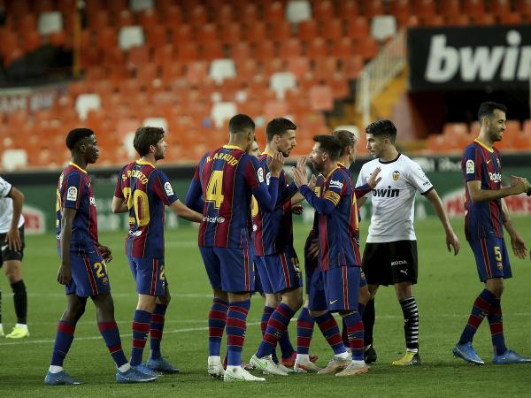 Futbalista Lionel Messi sa teší so spoluhráčmi po výhre 3:2 v zápase proti Valencii