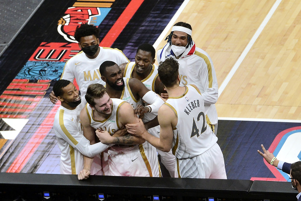 Basketbalista Luka Dončič (uprostred) z Dallasu Mavericks sa teší so spoluhračmi po vhodení víťaznej trojky na konci zápasu