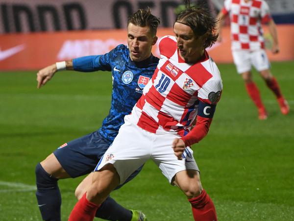 Kapitán Chorvátska Luka Modrič (vpravo) a Slovák Peter Pekarík (vľavo) bojujú o loptu