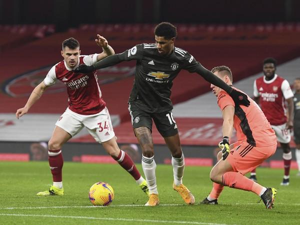 Marcus Rashford obchádza dvojicu hráčov Arsenalu