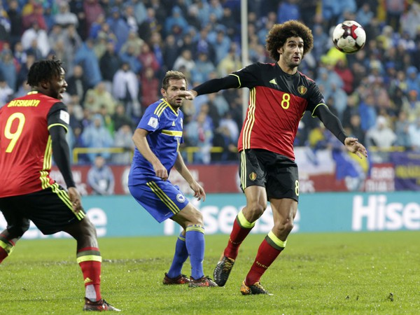 Belgický hráč Marouane Fellaini (vpravo) uniká s loptou pred Senadom Luličom z Bosny