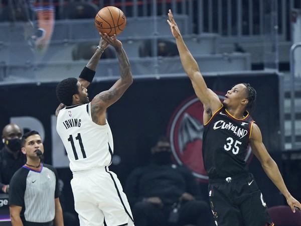 Na snímke vľavo hráč Nets Kyrie Irving a hráč Clevelandu Isaac Okoro