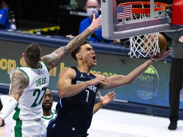 Hráč Dallasu Mavericks Dwight Powell (vpravo) strieľa na kôš cez Daniela Theisa z Bostonu Celtics v basketbalovom zápase zámorskej NBA v Dallase