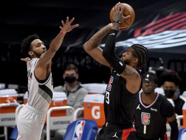 Hráč Los Angeles Clippers Paul George (vpravo) strieľa na kôš cez Derricka Jonesa z Portlandu Trail Blazers