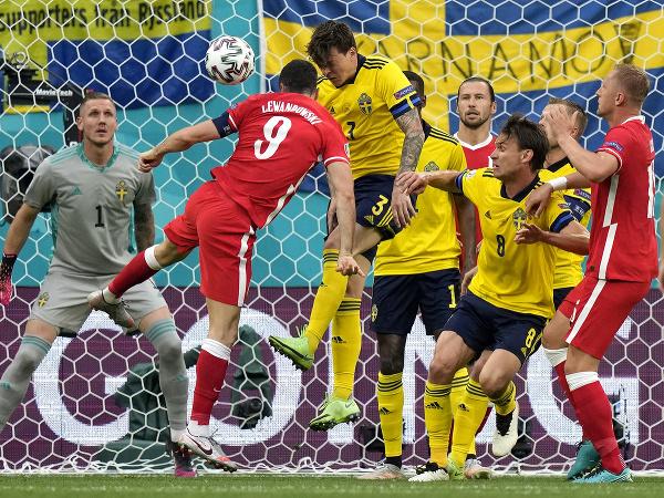 Poľský hráč Robert Lewandowski (druhý zľava) hlavičkuje