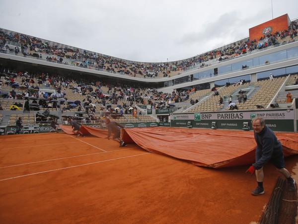 Usporiadatelia zakrývajú dvorec pre dážď počas semifinálového zápasu dvojhry mužov Dominic Thiem - Novak Djokovič