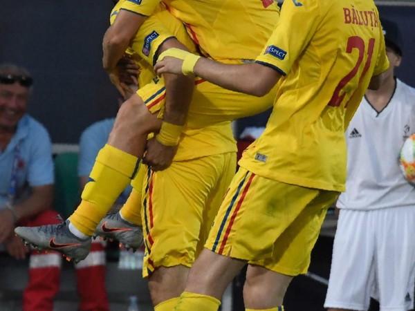 Na snímke vľavo hráč Rumunska Adrian Petre oslavuje gól