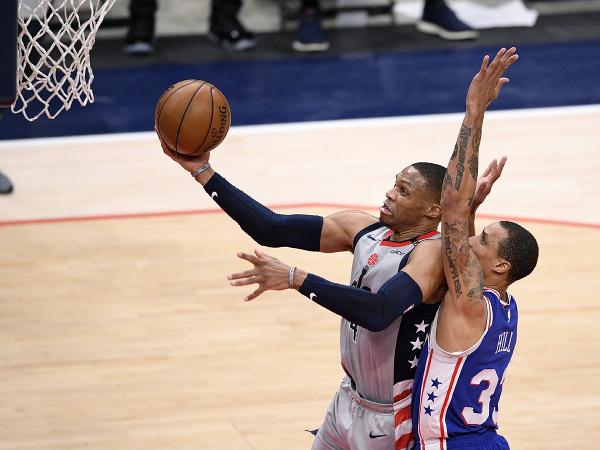 Hráč Washingtonu Wizards Russell Westbrook (vľavo) strieľa na kôš cez Georgea Hilla z Philadelphie 76ers