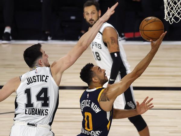Hráč Utahu Jazz Nigel Williams-Goss (vpravo) strieľa na kôš cez Drewa Eubanksa zo San Antonia Spurs