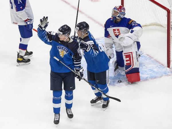 Fínski hokejisti  Juuso Parssinen (27) a Roni Hirvonen sa tešia z gólu, vpravo slovenský brankár Samuel Hlavaj