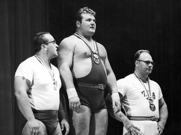Na archívnej snímke z roku 1964  olympijský víťaz vo vzpieraní Leonid Žabotinskij (uprostred) zo Sovietskeho zväzu, strieborný medailista Jurij Vlasov (ZSSR) a bronzový medailista Američan Norbert Schemansky stoja na pódiu počas odovzdávania medailí v naj