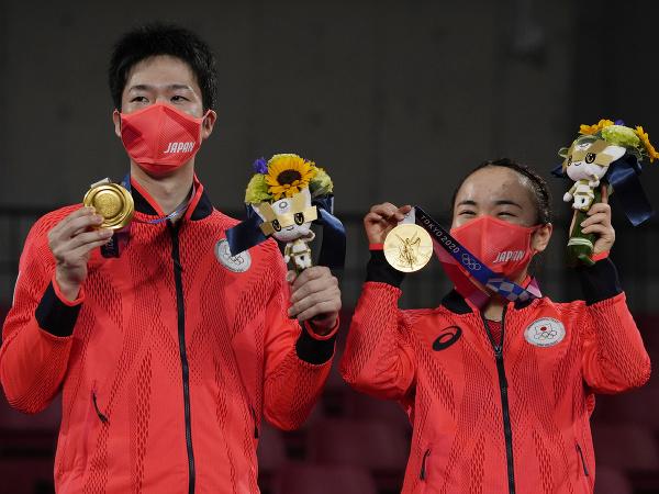 Japonskí stolnotenisoví športovci Jun MIzutani a Mima Ito oslavujú zlaté medaily